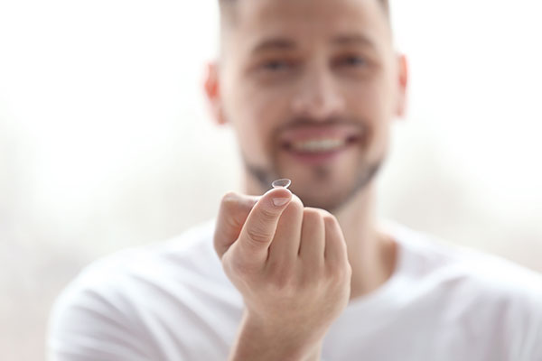 man holding contact lens